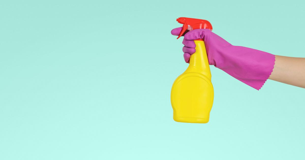 turquoise background yellow spray bottle held by pink rubber glove hand ready to spray